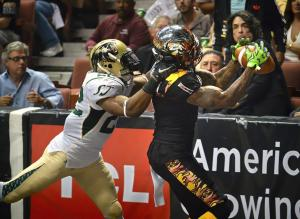 LA KISS Donovan Morgan completes a touchdown pass with San Jose SaberCats' Fredrick Obi behind him in the second quarter of an arena football game at the Honda Center. STEVEN GEORGES, CONTRIBUTING PHOTOGRAPHER ///ADDITIONAL INFORMATION: The LA KISS host the San Jose SaberCats in an arena football game for the last regular season match at the Honda Center. LAKiss.0809 8/8/15